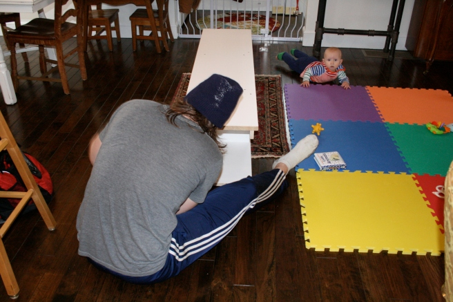 Matt putting the bookcases together in the middle of our living area with Baby L looking on. Look how little he was!