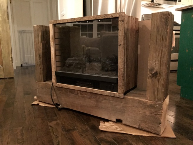 The front of the electric fireplace wrapped in barn beams without the top on.